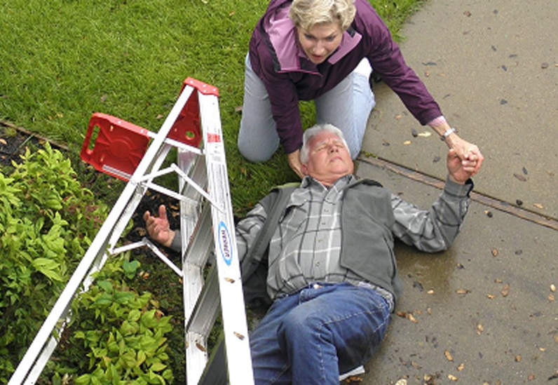 Man fallen down next to ladder getting assistance from wife